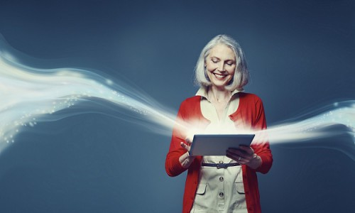 Composite image of senior woman standing with digital tablet with swirl of light rising from in