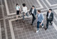Multiracial group of business people walking and talking together in a modern office building foyer. View from elevated position.